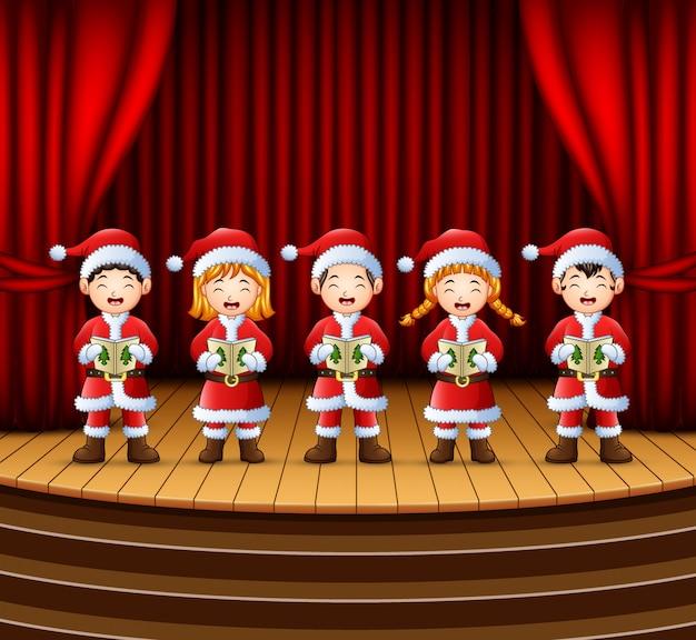 Groep kinderen die kerstmishymnes op het stadium zingen
