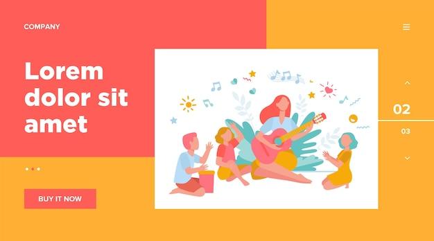 Groep kinderen handen klappen bij hun leraar gitaar spelen.