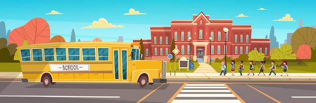Groep leerlingen mix race wandelen naar school gebouw van gele bus