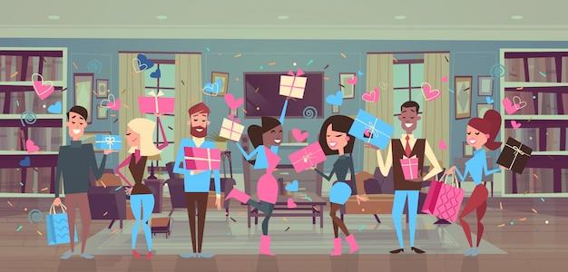 Groep mensen die geschenk dozen over hart vormen mannen en vrouw valentines day party celebration