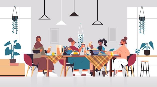 Groep mix race vriendinnen zittend aan tafel bespreken tijdens het diner in de club van vrouwen meisjes ondersteunen elkaar woonkamer interieur horizontale portret vectorillustratie