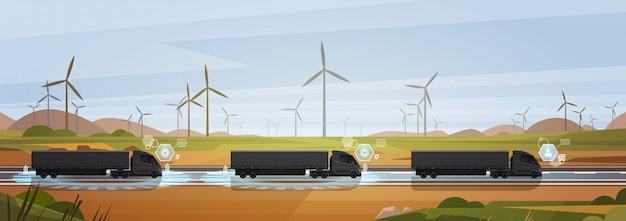 Groep zwarte ladingsvrachtwagen met aanhangwagens die op plattelandsweg over horizontaal natuurlandschap drijven