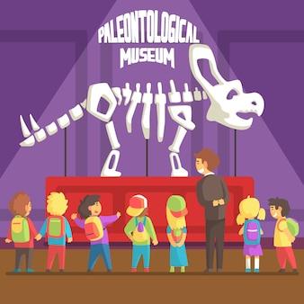 Groop van schoolkinderen in paleontologisch museum naast triceratops-skelet