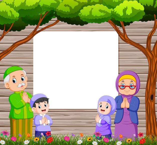 Grootmoeder en grootvader met hun kleinkind geven de groet van ied mubarak bij het lege bord