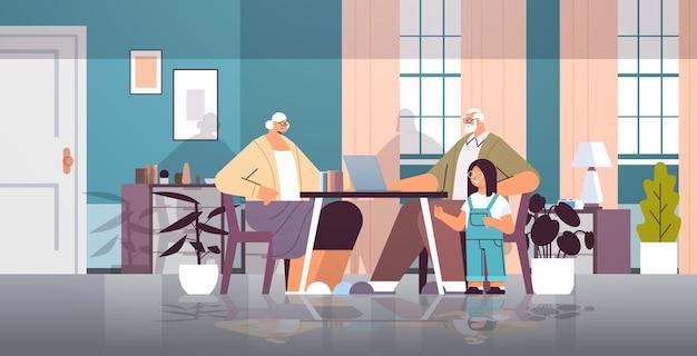 Grootouders met kleindochter met behulp van laptop sociale media netwerk online communicatie concept woonkamer interieur
