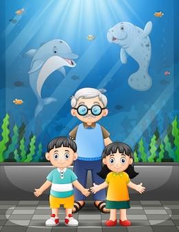 Grootvader en kinderen kijken naar zeedieren in een gigantisch aquarium
