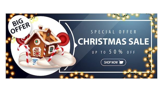 Grote aanbieding, kerstuitverkoop, tot 50 korting, blauwe kortingsbanner met slinger, knoop en kerstkoekhuisje
