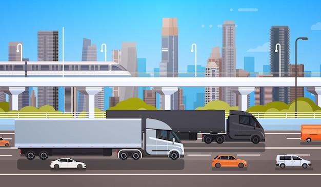 Grote cargo-vrachtwagenaanhangwagens op wegweg met auto's en vrachtwagen over moderne stadsachtergrondverzending