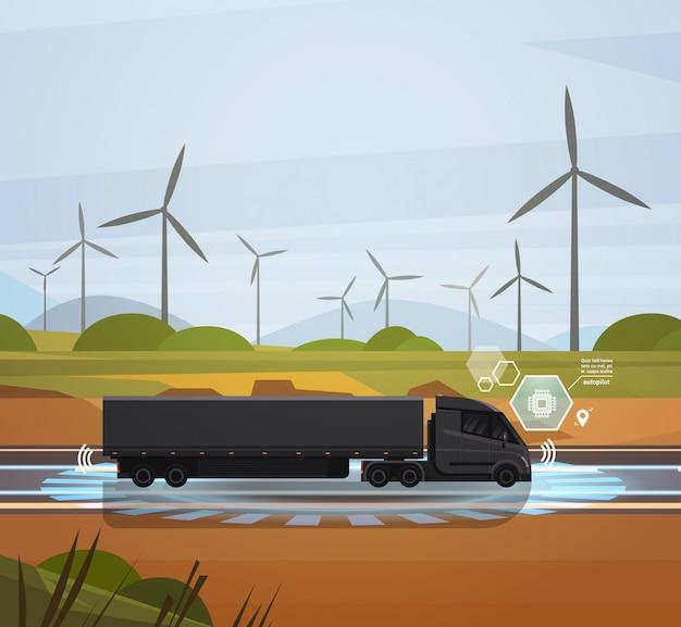 Grote semi vrachtwagenaanhangwagen die over gebied met het landschap van windtrubines drijft