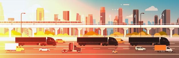Grote semi vrachtwagenaanhangwagens die in lijn op wegweg met auto's, vrachtwagen over stadsachtergrond drijven drijven