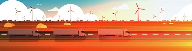 Grote semi vrachtwagenaanhangwagens die weg over het landschaps horizontale banner van de aardzonsondergang drijven