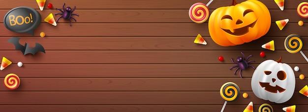 Halloween-banner met leuke halloween-pompoen, vleermuis, spin en suikergoed op hout