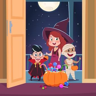 Halloween trick or treat. kinderen in halloween-kostuums met snoepjes in de deuropening.