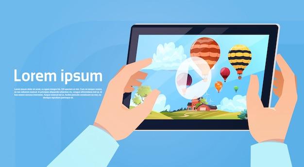 Hand die de moderne videotoestelhorloge van de tablet van kleurrijke luchtballons houden die in hemel vliegen