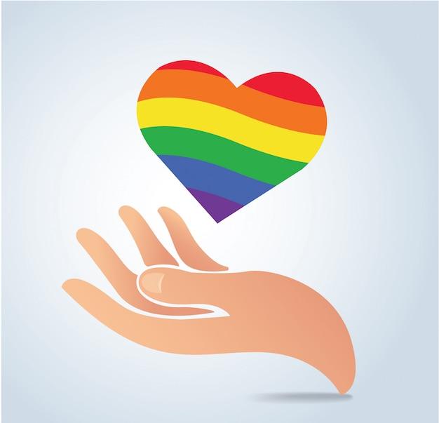 Hand die de regenboogvlag in hartvorm houdt