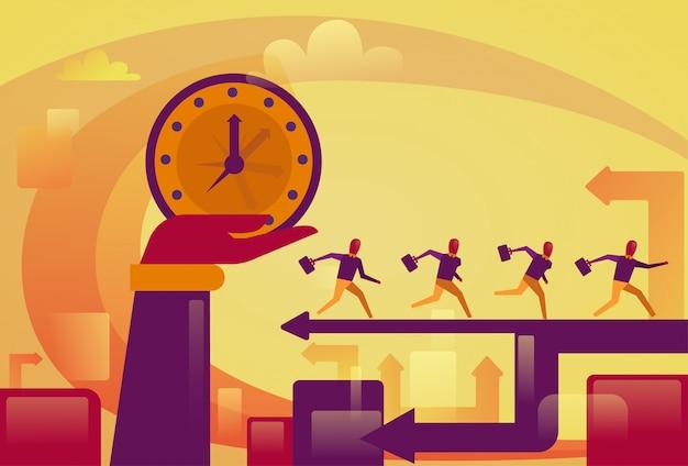 Hand die groot horloge over het lopende concept van de mensen deadline van mensen houden