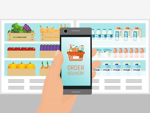 Hand die mobiele telefoon met mand op het scherm houdt. supermarkt boodschappen bezorgservice applicatie. online boodschappen doen.