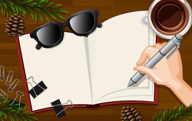 Hand die op leeg boek dicht op bureauachtergrond schrijven met koffiekop en sommige bladerensteunen