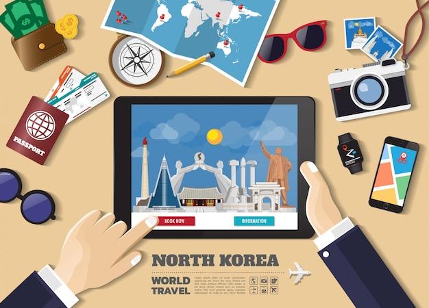 Hand die slimme tablet het boeken reisbestemming houdt. beroemde plaatsen in noord-korea.