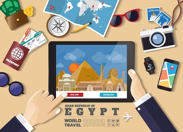 Hand die slimme tablet het boeken reisbestemming houdt. egypte beroemde plaatsen.