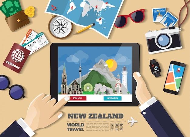 Hand die slimme tablet het boeken reisbestemming houdt. nieuw-zeeland bekende plaatsen