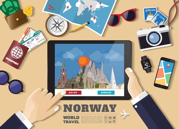Hand die slimme tablet het boeken reisbestemming houdt. noorwegen beroemde plaatsen
