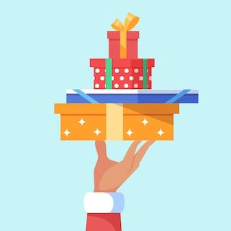 Hand die van de kerstman een grote stapel veel dozen van de kerstmisgift houdt.