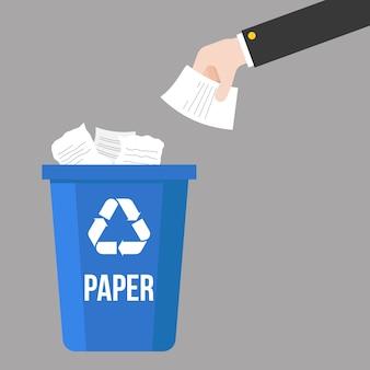 Hand gegooid papierafval en kleurrijke prullenbak