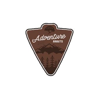 Hand getekende vintage camping badge en wandelen label met bergen, bos, klimhelm en typografie designelementen. quote tekst-avontuur wacht. oude stijl patch. rustieke stempel vector sjabloon.