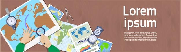 Hand hold vergrootglas studiekaarten tophoekweergave van werkplekgeografie en cartografieconcept