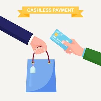 Hand houden creditcard of bankpas en boodschappentas