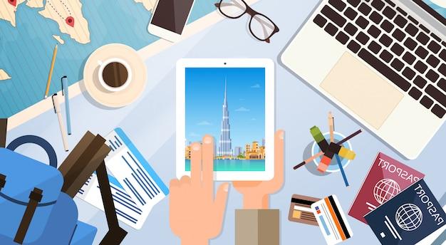 Hand houden tabletcomputer met dubai skyline panorama, traveler werkplek met paspoorten top hoek v
