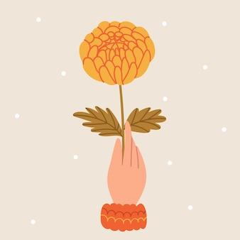 Hand houdt een dahlia vastherfststemming sneeuw rond de herfstbloem