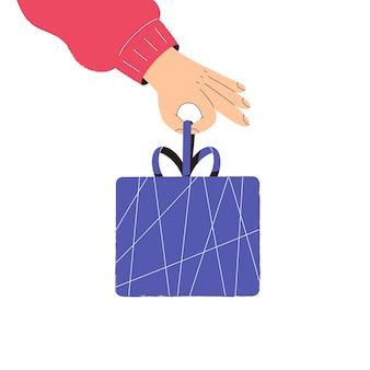 Hand houdt een kerstcadeaudoos vast, het concept van voorbereiding op de wintervakantie
