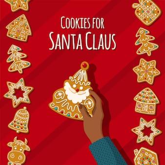 Hand houdt een peperkoek santa claus zelfgemaakte kerstkoekjes