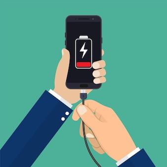Hand houdt een telefoon vast met een bijna lege batterij