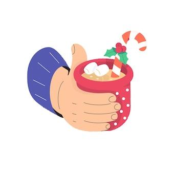 Hand houdt een warme kerstdrank mok met warme chocolademelk of koffie met snoepriet marshmallow