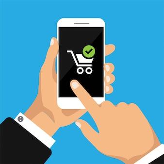 Hand houdt smartphone met winkel wagen op smartphone scherm.