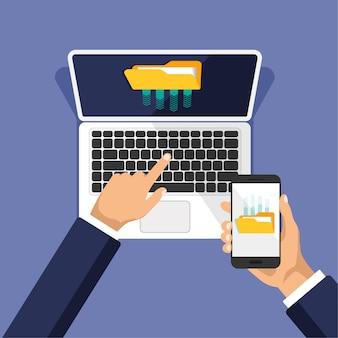 Hand houdt telefoon, klikt op laptop toetsenbord. zakenman uploadt bestanden naar cloudopslag of computer.