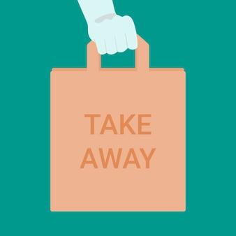 Hand in handschoen houden eco papieren pakket met inscriptie take away. afhaalmaaltijden tijdens de uitbraak van het coronavirus.