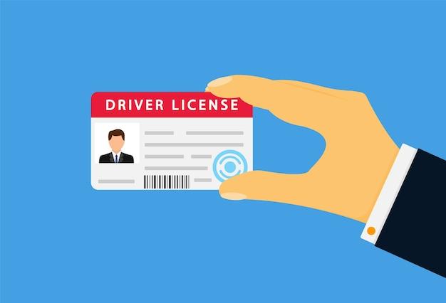 Hand met een rijbewijs dat op blauw wordt geïsoleerd
