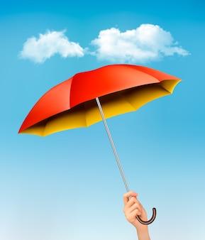 Hand met een rode en gele paraplu tegen een blauwe hemel met wolken.