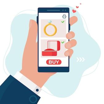 Hand met een telefoon met scherm voor het kopen van trouwring. online winkelen