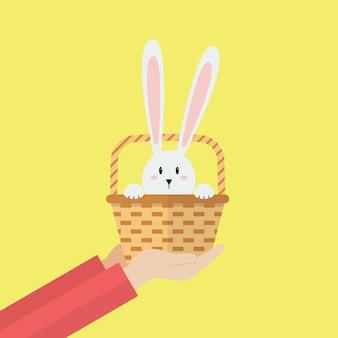 Hand met konijn in de mand