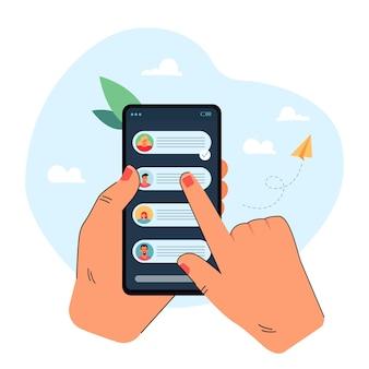 Hand met mobiele telefoon met chatberichten op het scherm