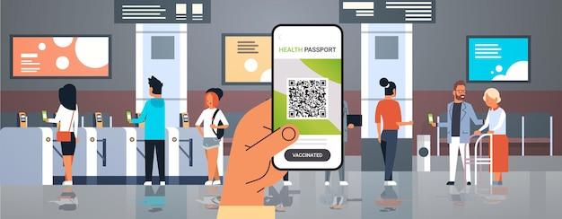 Hand met smartphone met digitaal immuniteitspaspoort met qr-code op scherm risicovrije covid-19 pandemie