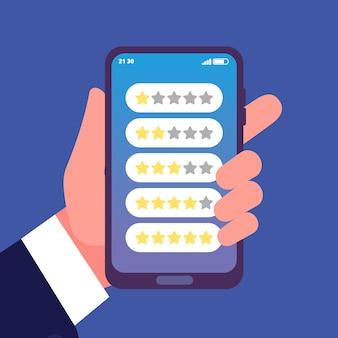 Hand met smartphone met feedback- of beoordelingssterren