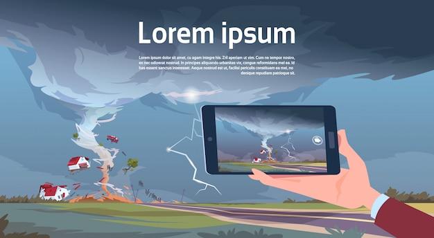 Hand met tablet filmen draaien tornado boerderij orkaan landschap vernietigen van storm waterspout in platteland natuurramp concept