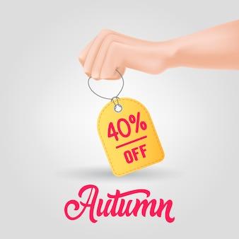 Hand met tag met herfst, veertig procent korting op belettering