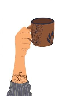 Hand met tatoeage houdt een kopje thee.